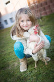 With hen on backyard. Young girl playing with a hen on the backyard Royalty Free Stock Photo