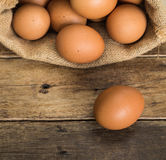 Hen eggs in brown gunny sack. On wooden table Stock Images