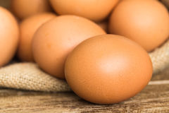 Hen eggs in brown gunny sack on wooden table. Close up Royalty Free Stock Photo