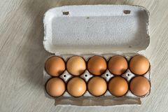 Hen eggs in open cardboard egg carton on kitchen table light copy space background. Healthy organic food and diet concept.  stock image