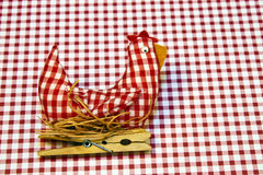 Hen fabric decoration. Stuffed fabric hen on a next made out of red and white gingham fabric over a ginham background Royalty Free Stock Image