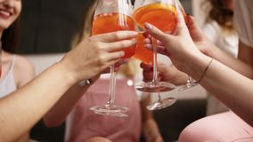 Hen party. Aim footage of a clinking with cocktails in girls hands. Female friends tell gossip and having fun. Laughing