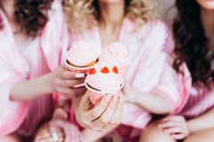Hen-party. Party for girls. Girlfriends eat pink airy cheesecakes before the wedding ceremony in pink pajamas. royalty free stock photos