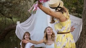 Hen party in the green garden. Girls friends are meeting their friend. Girl in yellow dress and summer hat happily. Coming to a picnic with friends stock video
