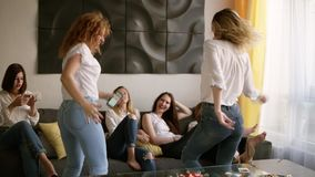 Hen party. Group of six attractive girls are having fun. Two girls are dancing in craziness. Identical casual clothes stock video