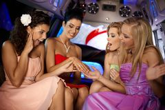 Hen party in limousine. Girls looking at her friends engagement ring Stock Photo