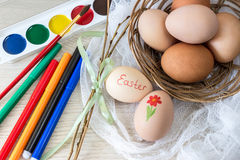 Hen`s eggs is prepared for painting with paints gouache and food markers for Easter. Stock Image