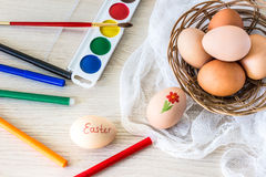 Hen`s eggs is prepared for painting with paints gouache and food markers for Easter. Royalty Free Stock Images