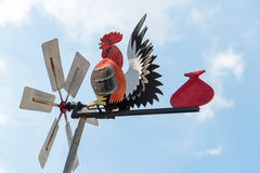 Hen-shaped weather vane over the top of a pointy-roofed house ag. Ainst cloudy blue sky stock photography