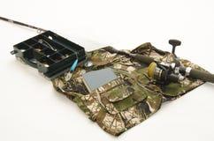 Hengel met spoel en visserijtoebehoren op camouflage jacke Stock Foto's