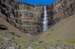 Hengifoss is the second highest waterfall on Iceland. The most s. Pecial thing about the waterfall are multicolored layers in the basalt rock behind waterfall Stock Images