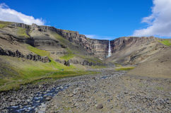 Hengifoss is the second highest waterfall on Iceland. The most s. Pecial thing about the waterfall are multicolored layers in the basalt rock behind waterfall Stock Photos