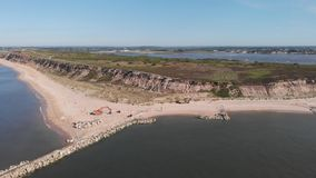 An aerial left sideway footage of the Hengistbury Head long Groyne restoration work scheme stock footage