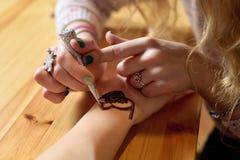 Hennè della pittura dell'artista di mehendi della giovane donna sulla mano Fotografie Stock
