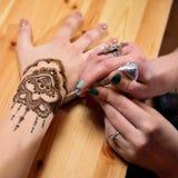 Hennè della pittura dell'artista di mehendi della giovane donna sulla mano Fotografia Stock Libera da Diritti
