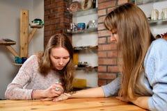 Hennè della pittura dell'artista di mehendi della giovane donna sulla mano Fotografia Stock
