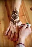 Hennè della pittura dell'artista di mehendi della giovane donna sulla mano Immagini Stock