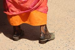 Henné tattoo in the feet of a woman. In a street of Khartoum Sudan wearing beautiful shoes Royalty Free Stock Photo
