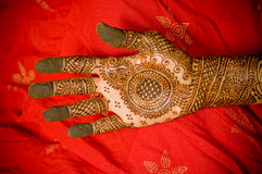 Henna. Closeup on hand with henna design. Red fabric as background color Royalty Free Stock Photography
