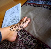 Henna Application & Designs. Detail of freshly applied henna to a woman's ankle and foot. Photograph includes a sketchbook of henna design patterns, and an royalty free stock images