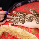 Henna art. A woman's hand being decorated with henna by an Arab beautician royalty free stock photos