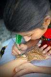 Henna artist. A young girl in rajasthan, india, drawing henna on to a friends hand Royalty Free Stock Photos