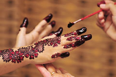 Henna. Artist applying henna tattoo on bride hands. Mehndi is traditional Indian decorative art. Close-up royalty free stock images