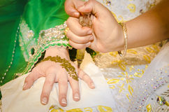 Henna being applied on bride's hand Stock Image