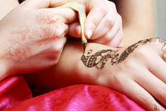 Henna being applied to hand Stock Photo