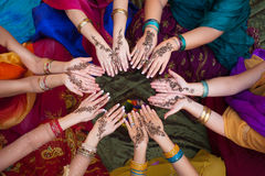 Henna Decorated Hands Arranged in a Circle. Six pairs of henna decorated female hands arranged in a circle on a colorful background Stock Photos