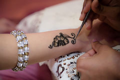 Henna detail being applied on arm Stock Image