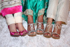 Henna on Feet. A bride's feet are decorated with henna and silver shoes. Her friends have on gold and pink shoes comparing the feet Stock Photography
