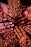 Henna hand paintings. Many hands, decorated with traditional Indian henna paintings are placed together in a circular formation stock image