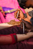 Henna mehndi ceremony. Indian bride getting henna mehndi designs on her hand for the wedding stock photo