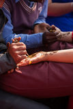 Henna mehndi ceremony. Indian bride getting henna mehndi designs on her hand for the wedding royalty free stock photo