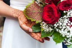 Henna på en brudhand med blommabuketten arkivbild