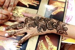 Henna Painting. Painting henna on the back of the hand of a lady in a bazaar stock photography
