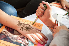Henna paste or mehndi application on female hand Royalty Free Stock Photography