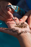 Henna pattern painted on woman's hand. A temporary henna tattoo applied by an artist Royalty Free Stock Images