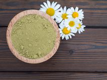 Henna powder in the coconut bowl and chamomile flowers Stock Photos