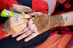 Henna tatoo. Drawing process of henna menhdi ornament on woman's hand. It is a dye prepared from the plant and to create the art of temporary body art or skin Stock Photos