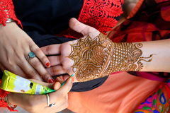 Henna tatoo. Drawing process of henna menhdi ornament on woman's hand. It is a dye prepared from the plant and to create the art of temporary body art or skin Royalty Free Stock Photos