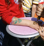 Henna tattoo. Girl is getting a henna tattoo on her hand Stock Photography