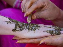 Henna Tattoo. Glitter is applied to a henna tattoo on the arm of a young female tourist in Meknes, Morocco. The tattoo is not permanent and lasts only a few royalty free stock images