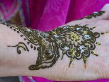 Henna Tattoo. Glitter is applied to a henna tattoo on the arm of a young female tourist in Meknes, Morocco. The tattoo is not permanent and lasts only a few royalty free stock photo