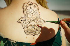 Henna tattoo mehendy painted on back. Hamsa royalty free stock image