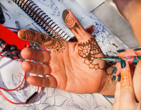 Henna Tattooing on Hand. Closeup of henna artist drawing designs with paste on the inside of a caucasian hand, outside at a festival royalty free stock photos