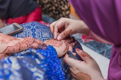 Malay Wedding Henna With Jewels. The henna tattooist assisting the bride in the touch up of her wedding henna and installing additional blings stock images