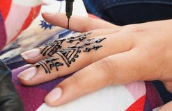 Henna tattoos being put on girls hand in Morocco. Henna tattoos being put on hands in Morocco stock image