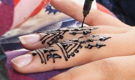 Henna tattoos being put on girls hand in Morocco. Henna tattoos being put on hands in Morocco stock photos